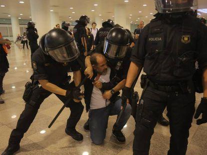 Polícias catalães retêm a um homem no Aeroporto do Prat.