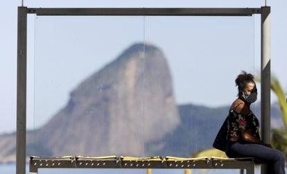 Mulher usa máscara em um ponto de ônibus no Rio de Janeiro na última segunda-feira.