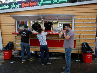 Três iraquianos em um restaurante de rua de Bagdá.