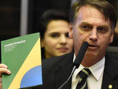 Bolsonaro segura um exemplar da Constituição em novembro de 2018.