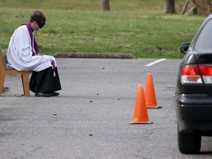 Um fiel, protegido dentro do carro, se confessa ao reverendo Scott Holmer, da igreja católica St. Edward, em Bowie, Maryland.