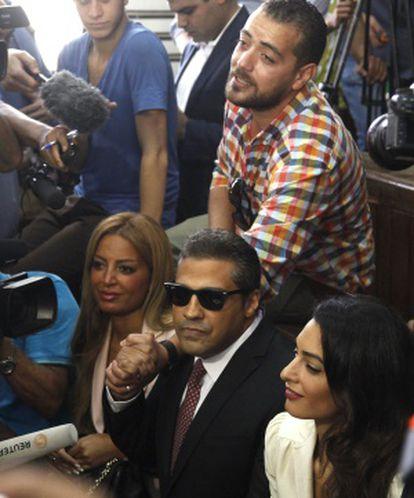 Os presos Mohamed Fahmy (centro) e Baher Mohamed (de pé, acima) falam com a imprensa ao lado da advogada Amal Clooney (direita) e da mulher de Fahmy.