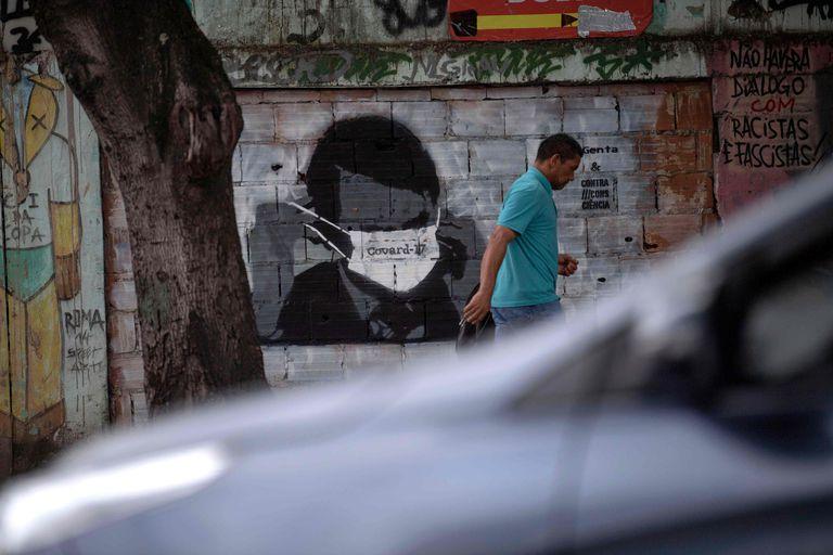 Homem caminha diante de grafite do presidente Bolsonaro, no Rio.