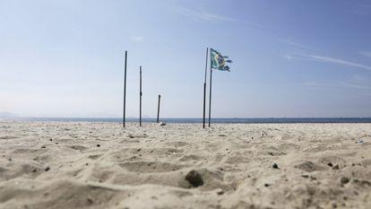 Bandeira brasileira na praia de Copacabana, fechada por causa da crise sanitária.