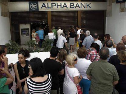 Atenienses fazem fila em frente a um caixa.