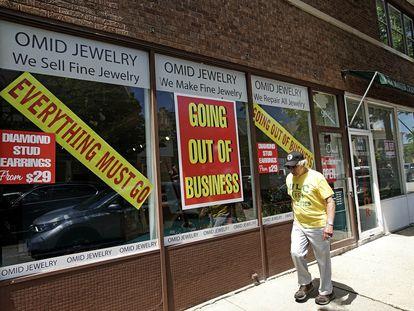 Homem passa na frente de uma loja que encerrou suas atividades, em Winnetka, em Illinois.