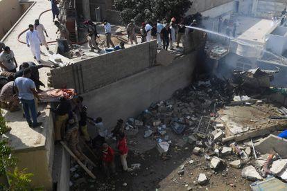 Voluntários retiram corpo de um dos passageiros de área atingida pelo avião, em 22 de maio de 2020.
