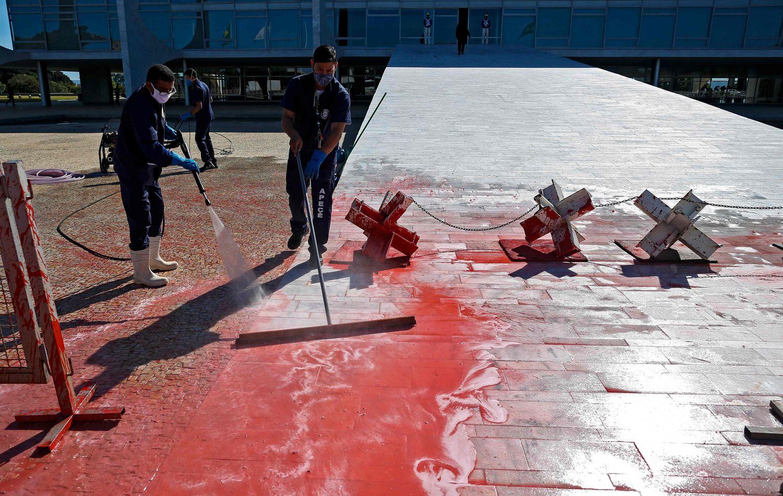 Funcionários limpam tinta vermelha despejada nesta segunda por manifestante na frente do Palácio do Planalto, em Brasília.