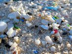 Pequenos fragmentos de plástico, dispersos entre na da praia.