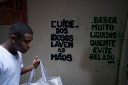 Um homem passa em frente a recados de conscientização sobre o coronavírus na Rocinha, Rio de Janeiro.