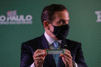 O governador de São Paulo, João Doria, segura uma caixa da CoronaVac durante uma coletiva de imprensa, em 7 de janeiro.