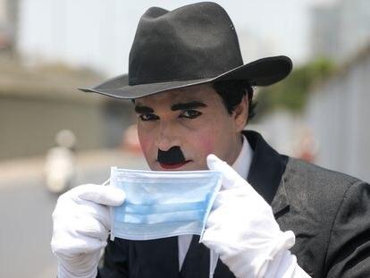 Imitador de Charlie Chaplin promove o uso da máscara para proteção contra o coronavírus numa rua de Mumbai, Índia, nesta sexta-feira.