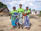 Marie (izquierda), Marinasy (centro) y Tsiampoizy (derecha) son tres mujeres de Ranomay. En la foto, muestran los paneles y las lámparas solares que ellas mismas instalan y reparan. Viajaron hasta India para formarse como ingenieras solares. Estas aldeanas, que no saben leer ni escribir, han dado luz a 155 hogares de su comunidad rural.