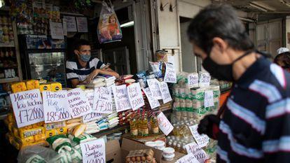 Vendedor espera clientes em uma mercearia de Caracas, Venezuela.