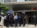 """(FILES) In this file photo taken on September 16, 2021, police officers look at people gathering at the Evergrande headquarters in Shenzhen, southeastern China, as the Chinese property giant said it is facing """"unprecedented difficulties"""" but denied rumours that it is about to go under. - Anxious investors, employees and suppliers describe a scramble inside teetering Chinese property giant Evergrande, in a crisis that has shaken public trust as it struggles to tide over a liquidity crunch. (Photo by Noel Celis / AFP) / TO GO WITH AFP STORY CHINA-ECONOMY-PROPERTY-EVERGRANDE,FOCUS BY BEIYI SEOW AND VIVIAN LIN"""