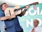 O presidente Jair Bolsonaro simula que o violão é uma arma durante um encontro com líderes políticos do Goiás, no sábado, 28 de agosto.