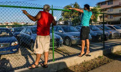 Cubanos observam um pátio com carros usados à venda.