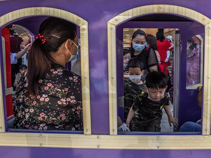 Mulheres com seus filhos em um parque de Pequim em 1º de junho.