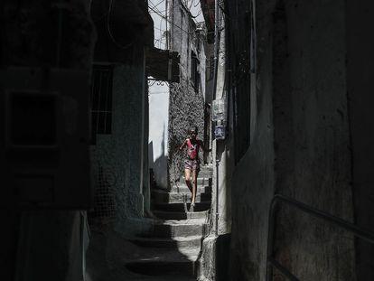 Mulher caminha por rua de favela no Rio de Janeiro.