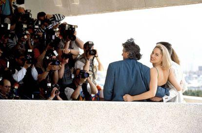 No Festival do Cannes de 1992, Sharon Stone, prestes a se tornar uma estrela mundial, dedica um sorriso a um fotógrafo enquanto seus colegas da equipe em 'Instinto Selvagem' posam para outros.