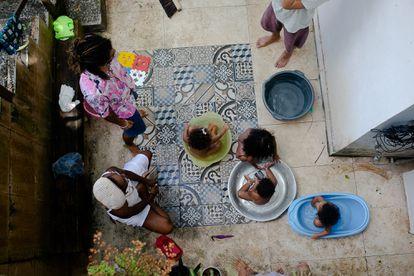 Isis Abena, de 35 anos, e sua filha Ainá, de 2, no pátio com seus vizinhos em Salvador.