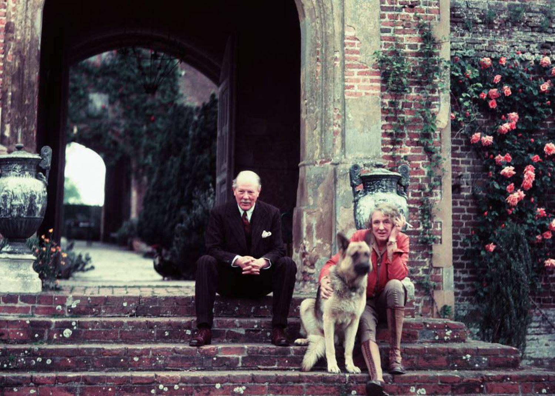 A poeta e romancista inglesa Vita Sackville-West com o marido, o diplomata Sir Harold Nicolson, no palacete de Sissinghurst, em Kent, em 1960, acompanhados por seu cachorro.