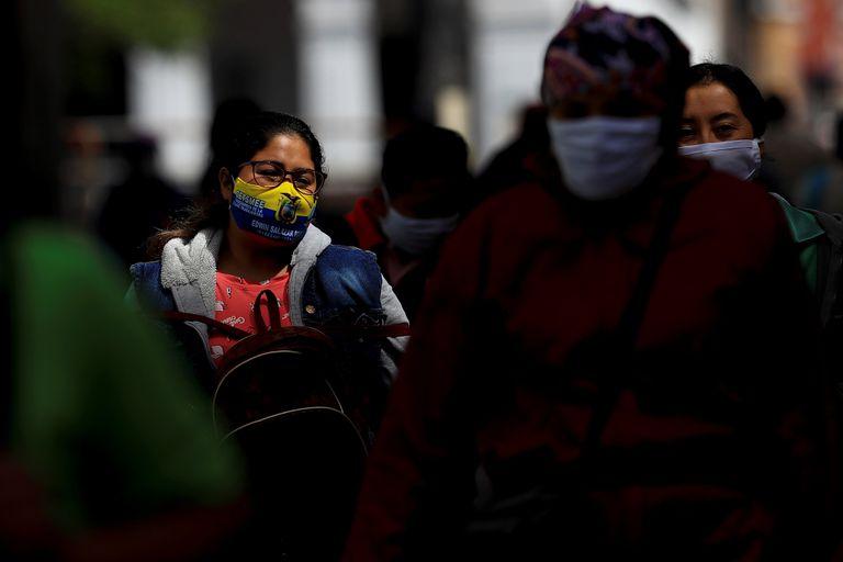 Várias pessoas com máscaras caminham por uma rua de Quito, em 25 de agosto.