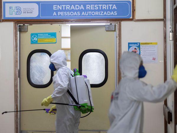 """BRA112. BRASILIA (BRASIL), 31/03/2020.- Miembros del ejército brasileño limpian en hospitales públicos este martes, en Brasilia (Brasil). Miembros del Comando Conjunto Planalto desinfectaron las áreas externas del Hospital Regional Asa Norte (Hran) y el Hospital de la Base Brasilia este martes por la mañana. El lunes, el ministro de Salud, Luiz Henrique Mandetta, dijo en una rueda de prensa junto a otros cuatro miembros del gabinete del presidente Jair Bolsonaro celebrada en el Palacio presidencial de Planalto, que el Gobierno iniciará un nuevo modelo de coordinación """"ampliado"""" de las acciones contra el coronavirus. EFE/ Joédson Alves"""