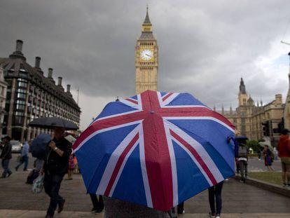 Uma pessoa passeia nas imediações do Parlamento Britânico com a bandeira do Reino Unido.