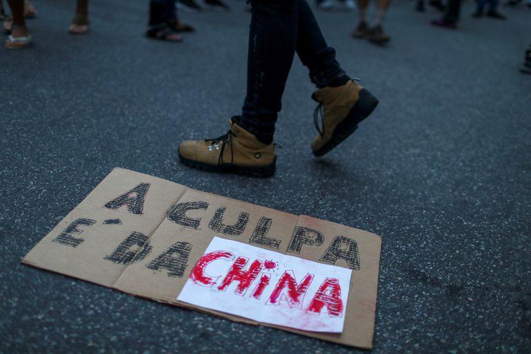 Manifestante bolsonarista caminha sobre cartaz durante protesto em frente ao consulado chinês no Rio de Janeiro contra uma suposta conspiração do país asiático para espalhar a covid-19 pelo mundo