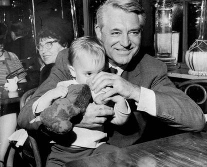 Cary Grant com sua filha Jennifer Grant no colo, em um restaurante, em 1967.