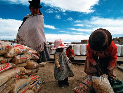 Família boliviana recebe alimentos em La Quiaca, um povoado argentino na fronteira com a Bolívia