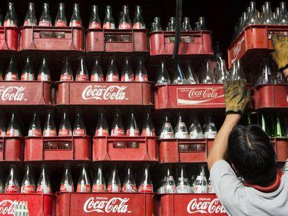 Funcionária empilha caixas de Coca-Cola na Cidade do México, em 2013