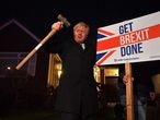 """(FILES) In this file photo taken on December 11, 2019 Britain's Prime Minister and Conservative party leader Boris Johnson poses after hammering a """"Get Brexit Done"""" sign into the garden of a supporter, with a sledgehammer as he campaigns with his team in Benfleet, east of London on December 11, 2019, the final day of campaigning for the general election. - The UK and European Union will on December 30 sign a mammoth trade pact to put the seal on their drawn-out Brexit divorce in the dwindling hours before they part ways definitively at the dawning of 2021. (Photo by Ben STANSALL / POOL / AFP)"""