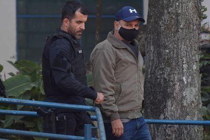 Queiroz é acompanhado por agente ao ser preso em junho.