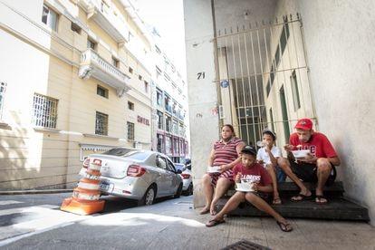 Maxwell Oliveira e Verônica Medeiros almoçam, junto com seus dois filhos, após receber doação de marmita de uma ONG, em São Paulo.