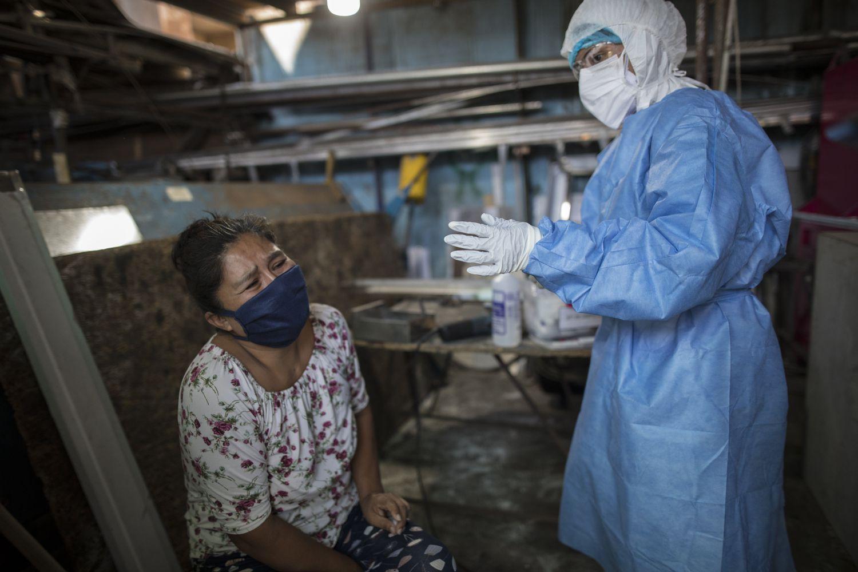 Mulher chora depois de coleta de sangue durante um teste de coronavírus em Lima, Peru.