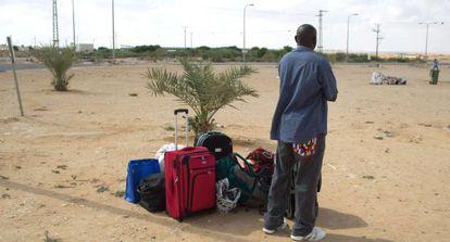 Um imigrante africano espera um meio de transporte depois de ser libertado no Neguev, no sul de Israel.