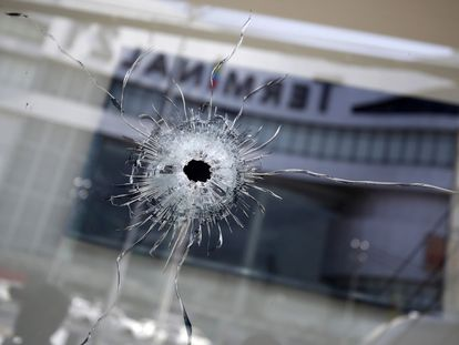 Buracos de bala são vistos ao lado do reflexo do prédio do shopping Terminal 21, o cenário de um tiroteio em massa em Nakhon Ratchasima, Tailândia