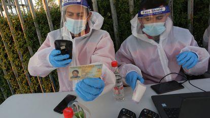 Pessoal médico no Chile verifica um documento de identidade como parte do protocolo contra a Covid-19 antes de um jogo de futebol.
