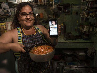 Yuliet Colón posa con la comida que preparó y su teléfono con su página de cocina de Facebook en su casa en La Habana, Cuba, el 2 de abril.