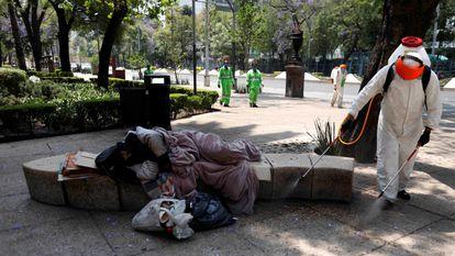 Agentes sanitários lavam praça no México, enquanto morador de rua dorme, em uma imagem de abril do ano passado.