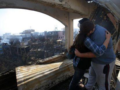 Um casal se abraça na frente da janela de casa.