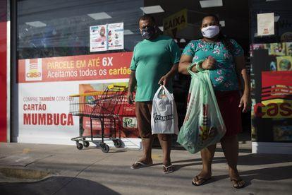 O casal Claudio Barbosa e Vagna Ferreira, após fazer compras no mercado com cartão Mumbuca, em Maricá.