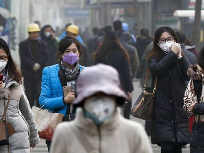 Mulheres vestem máscaras em Pequim.