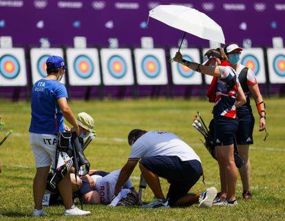 Svetlana Gomboeva é atendida durante a prova de tiro depois de desmaiar devido à insolação.