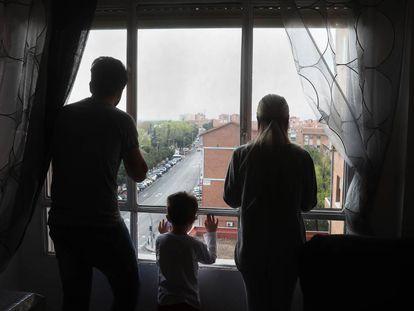 Miguel, Dara e seu filho olham pela janela do apartamento que ocupam.