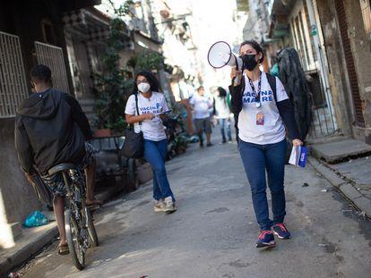 Voluntária usa megafone para convocar moradores do conjunto de favelas da Maré para se vacinarem contra a covid-19.