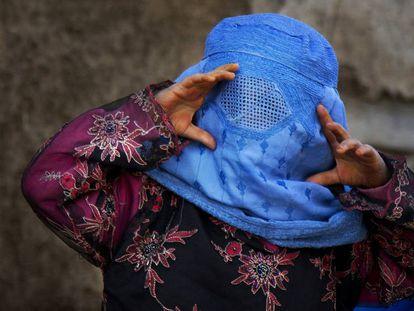 Uma menina afegã tenta ver através de sua burca.