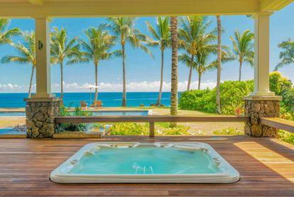 Um dos maiores luxos da casa é a banheira de hidromassagem ao ar livre, com vista para as palmeiras e o mar.